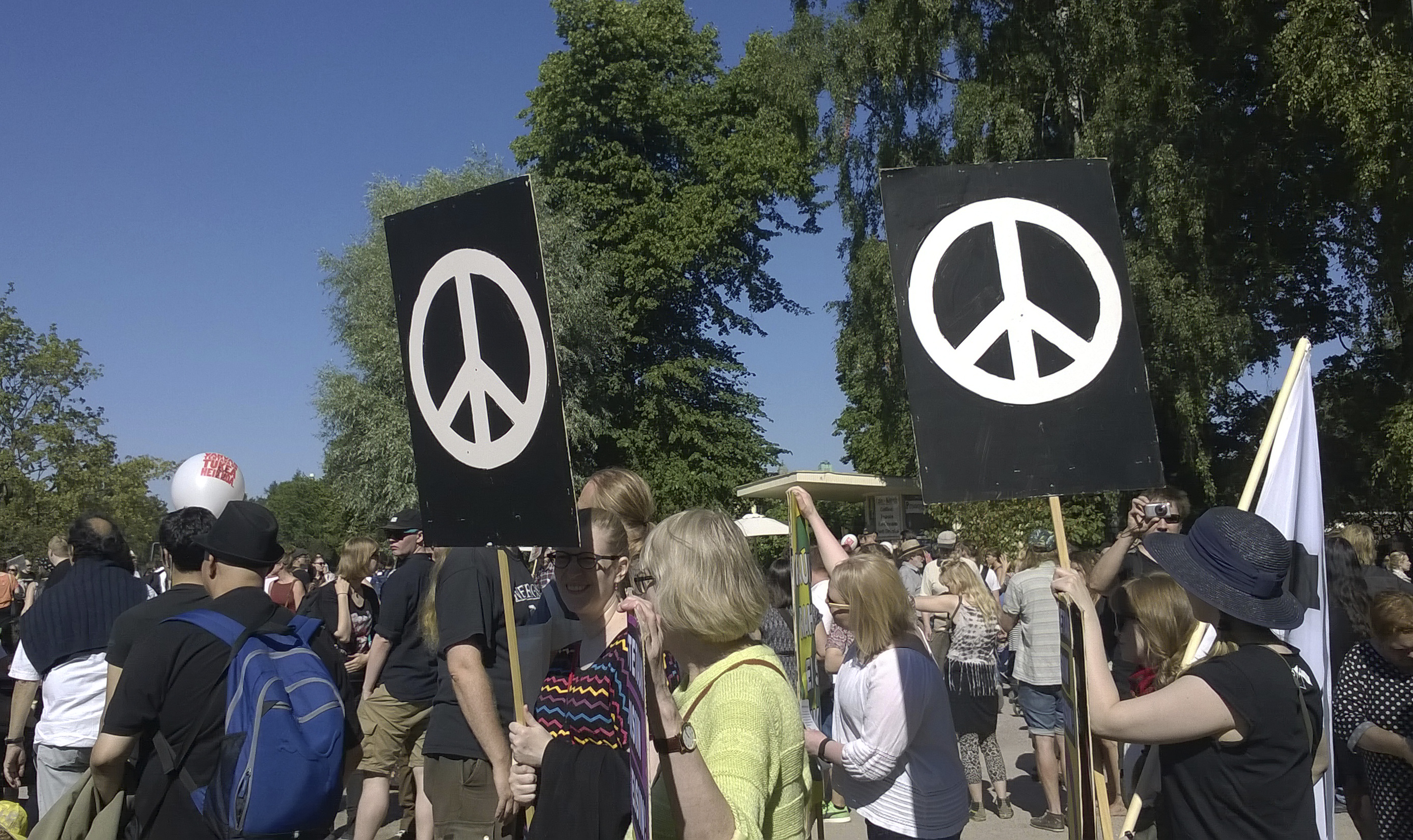 People in a demonstration with banners inclufing the peace sign.